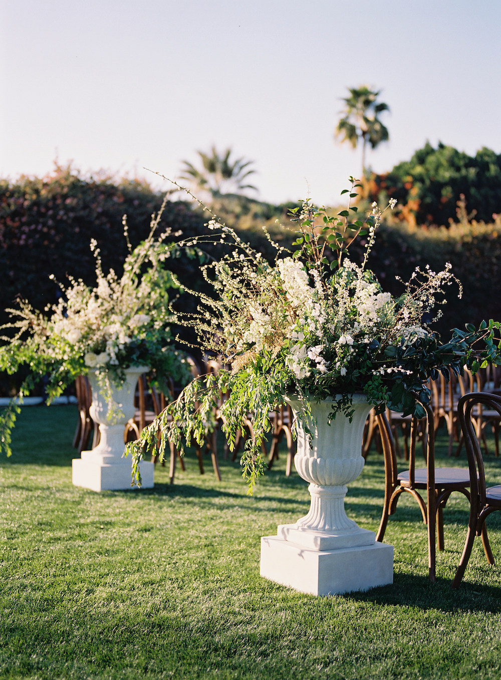 ivey trevor wedding large urns with overflowing flowers as outdoor ceremony decor
