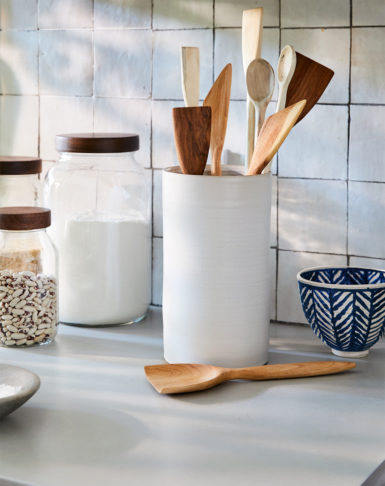 Turnco Wood Goods glass jars, Tracie Hervy crock, and Two Tree Studios hand-carved spatulas and spoons