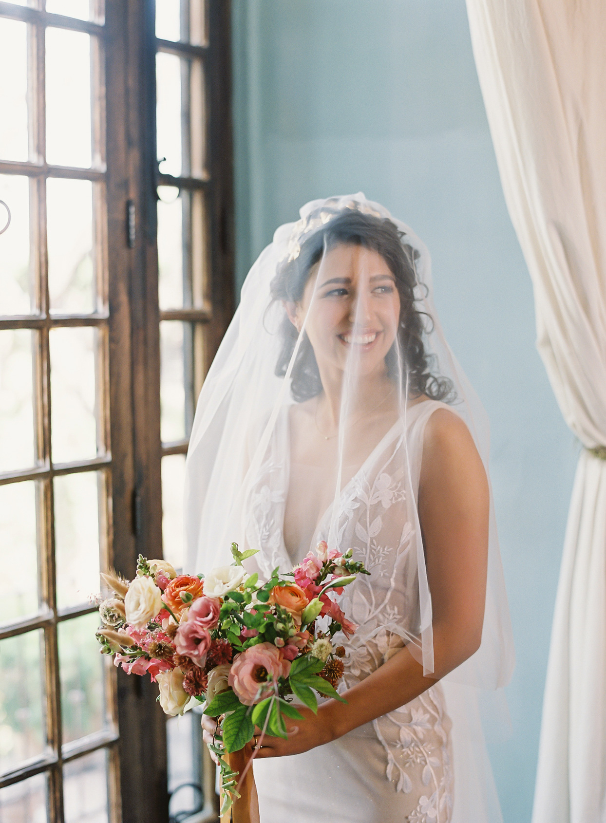 bride holding pink and orange floral bouquet standing by window