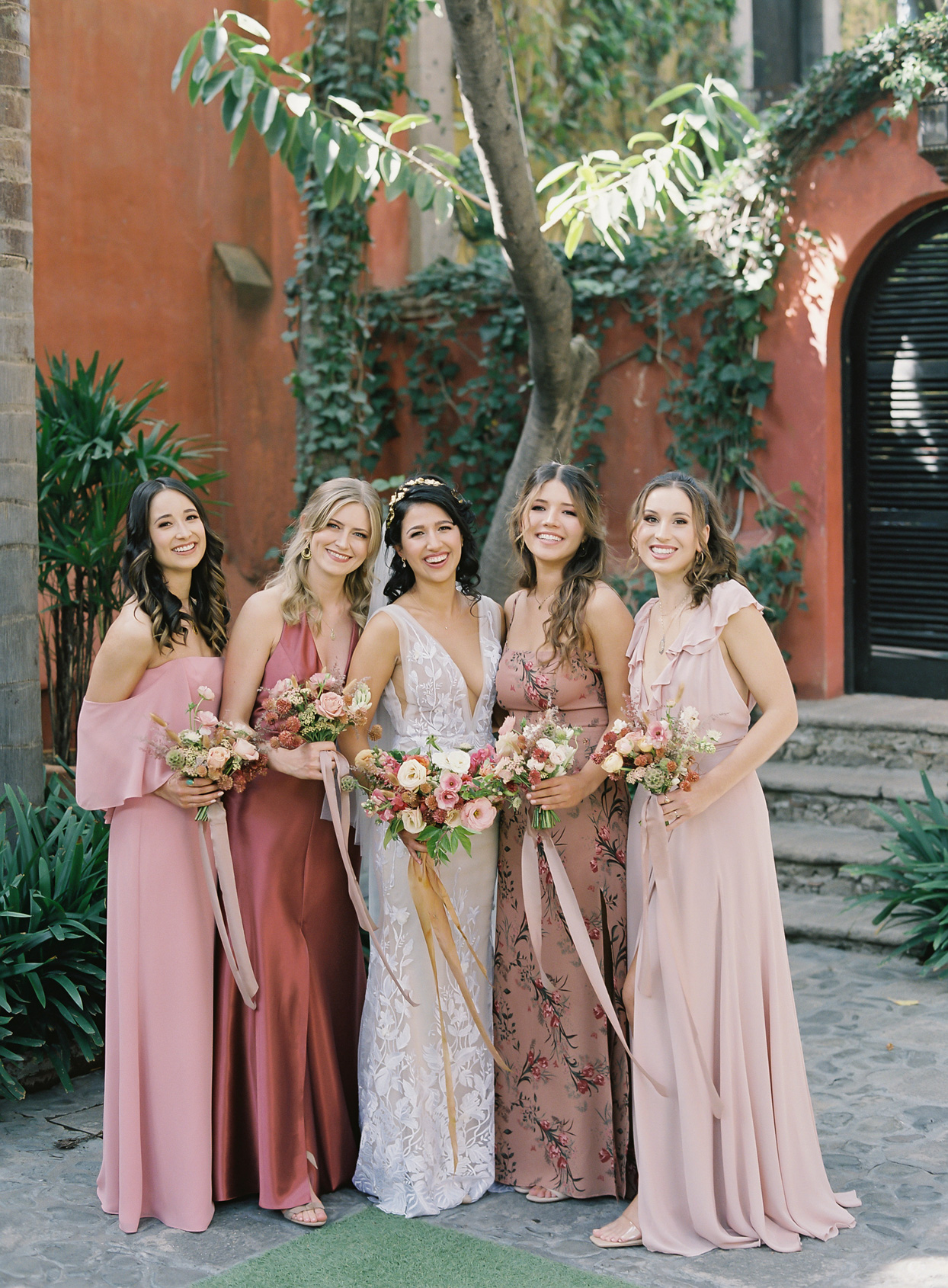bridesmaids in varied pink dresses with floral bouquets