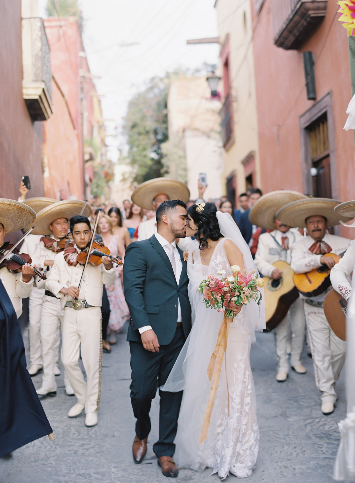 wedding couple kissing while walking down road with mariachi band