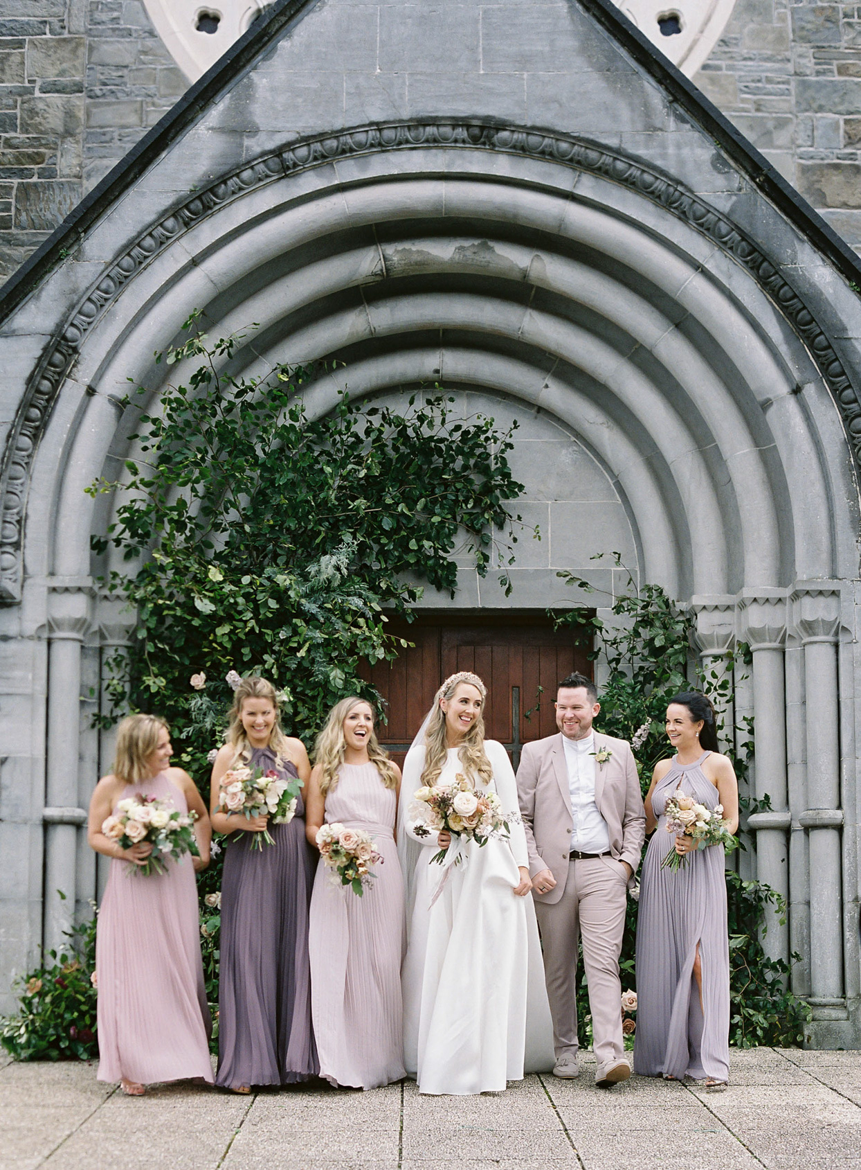 bride and wedding party in pink and purple pastels in front of church