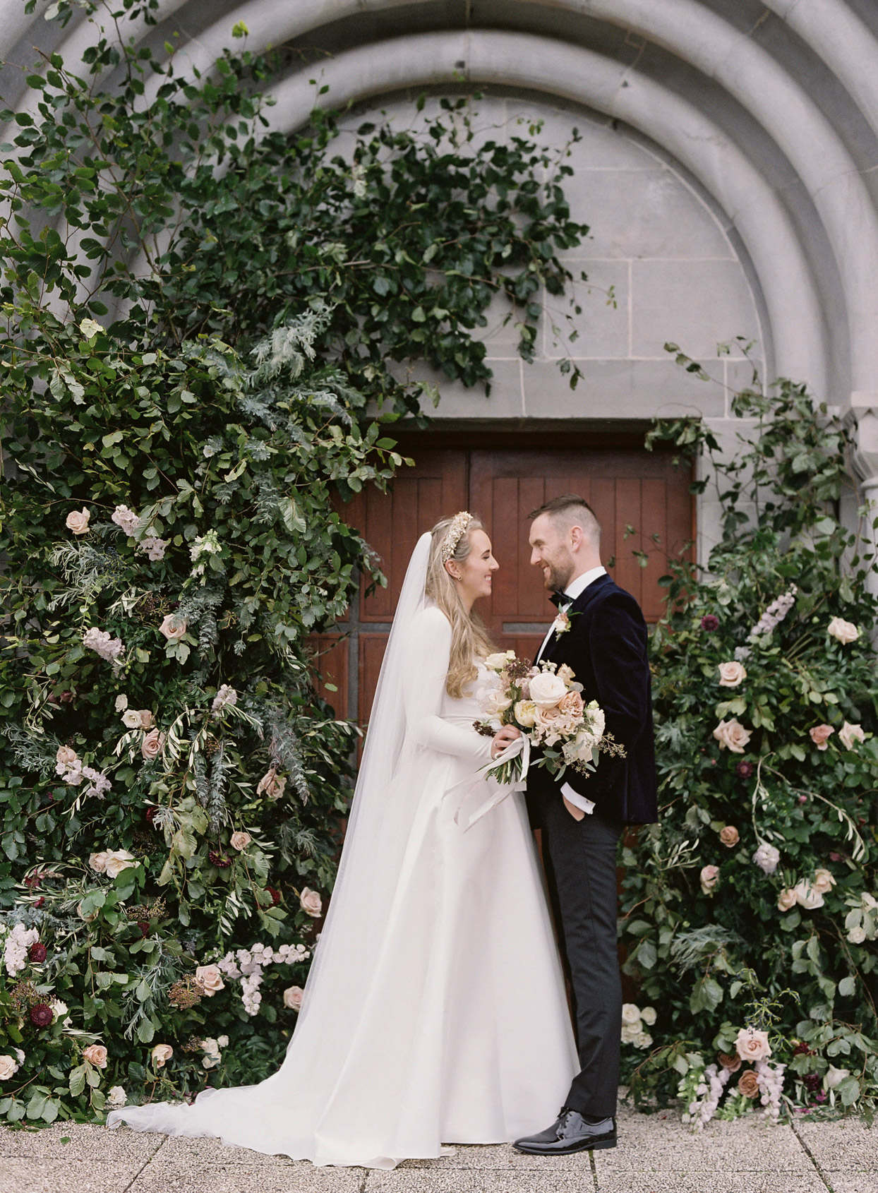 wedding couple standing together under greenery arch in front of chapel door