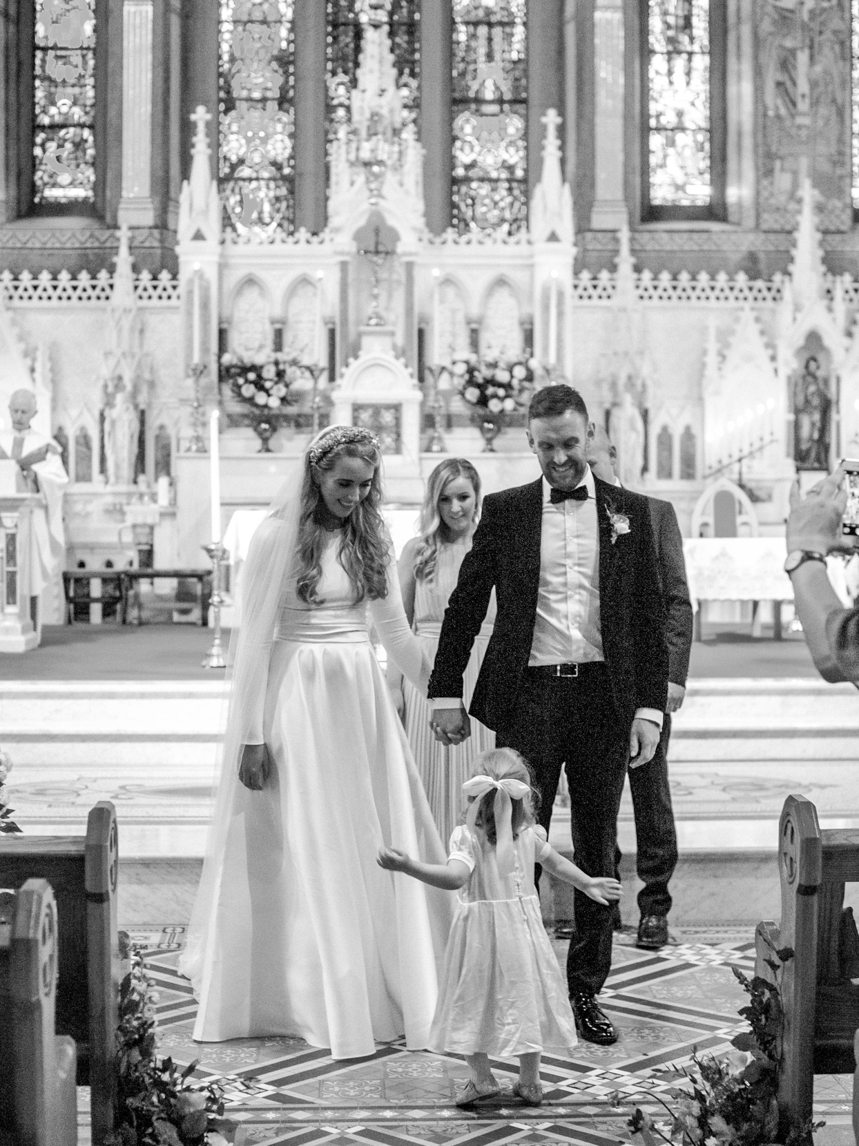 bride and groom holding hands in church with flower girl