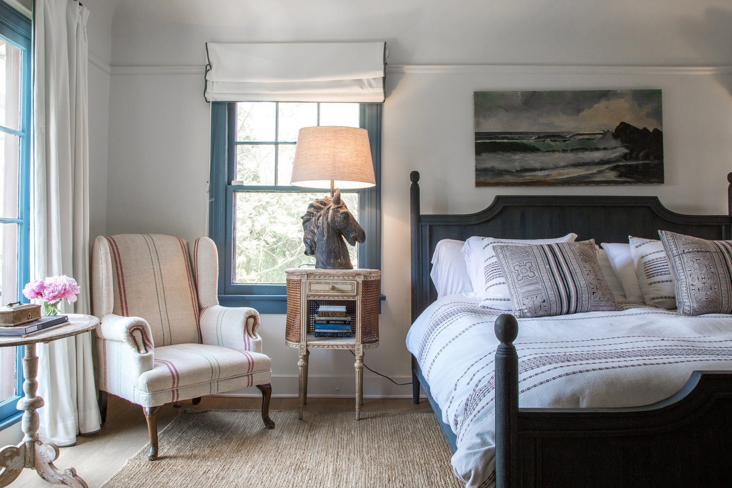 neutral-colored master bedroom with horse head lamp on bedside table