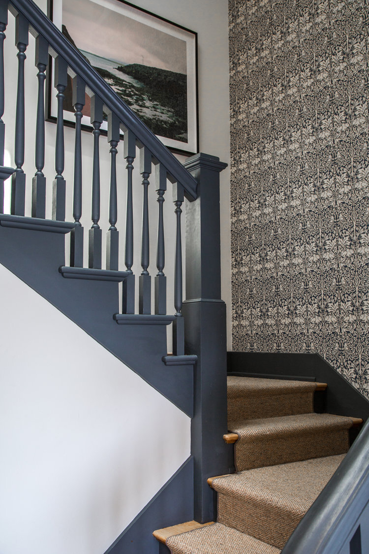 painted staircase in benjamin moores deep space and patterned wallpaper accent wall