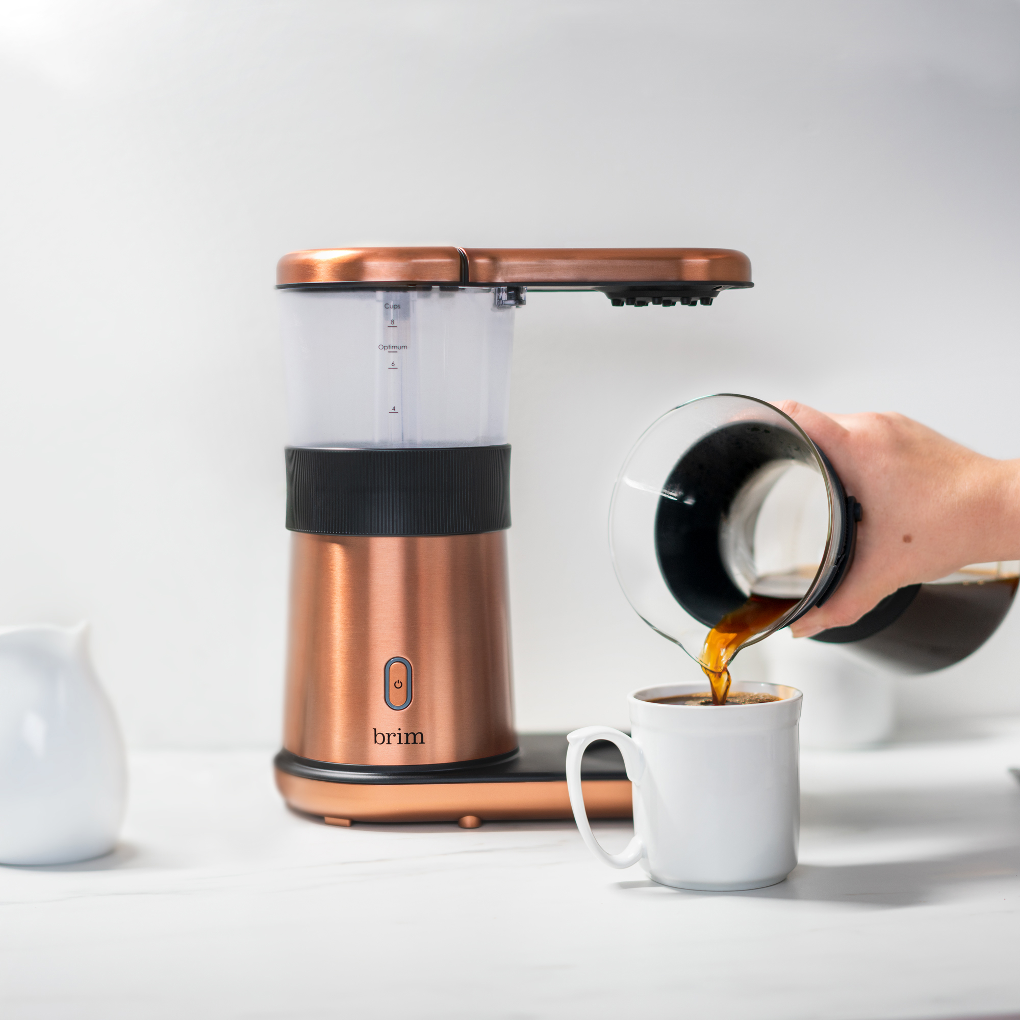 brim 8 cup pour over coffee machine in copper with hand pouring coffee from the carafe into a white mug