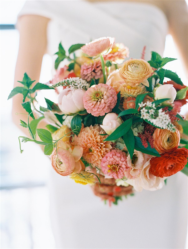 bride's pink, orange, and red floral wedding bouquet