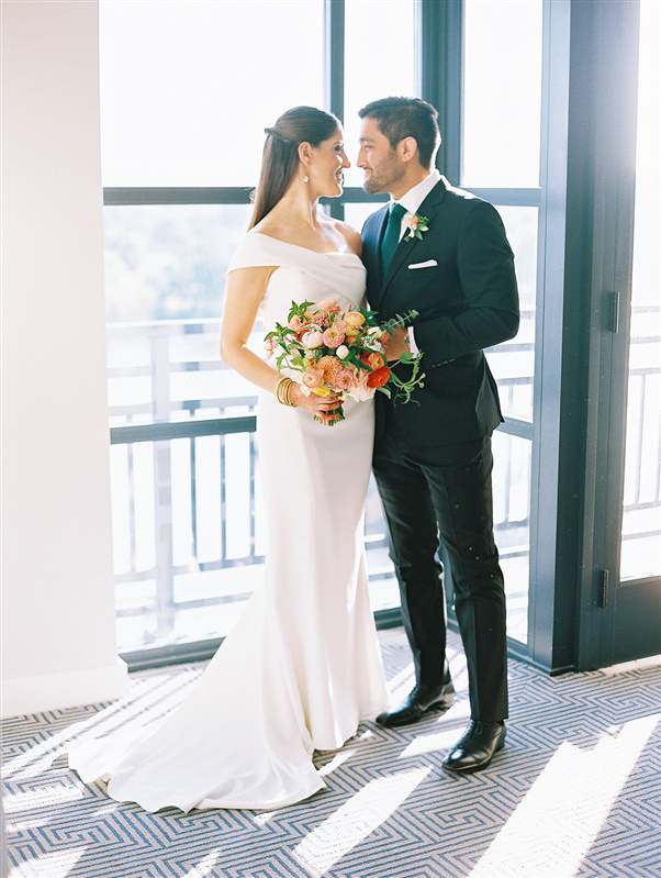 bride in white wedding dress and groom in black tux by window