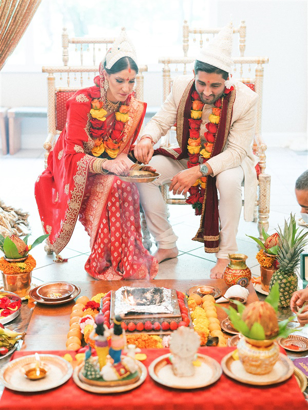 bride and groom performing traditional ritual during hindu ceremony