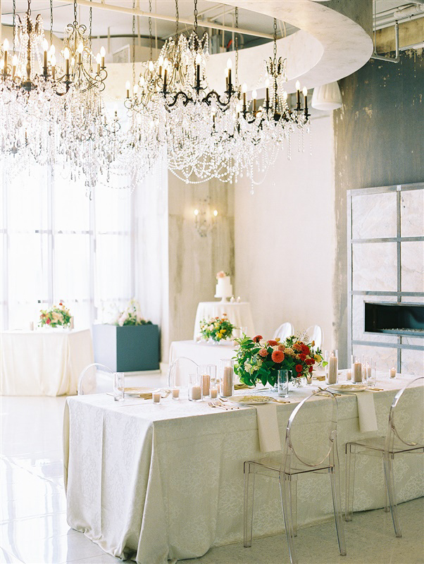 industrial wedding space with elegant chandeliers and gold and white decor