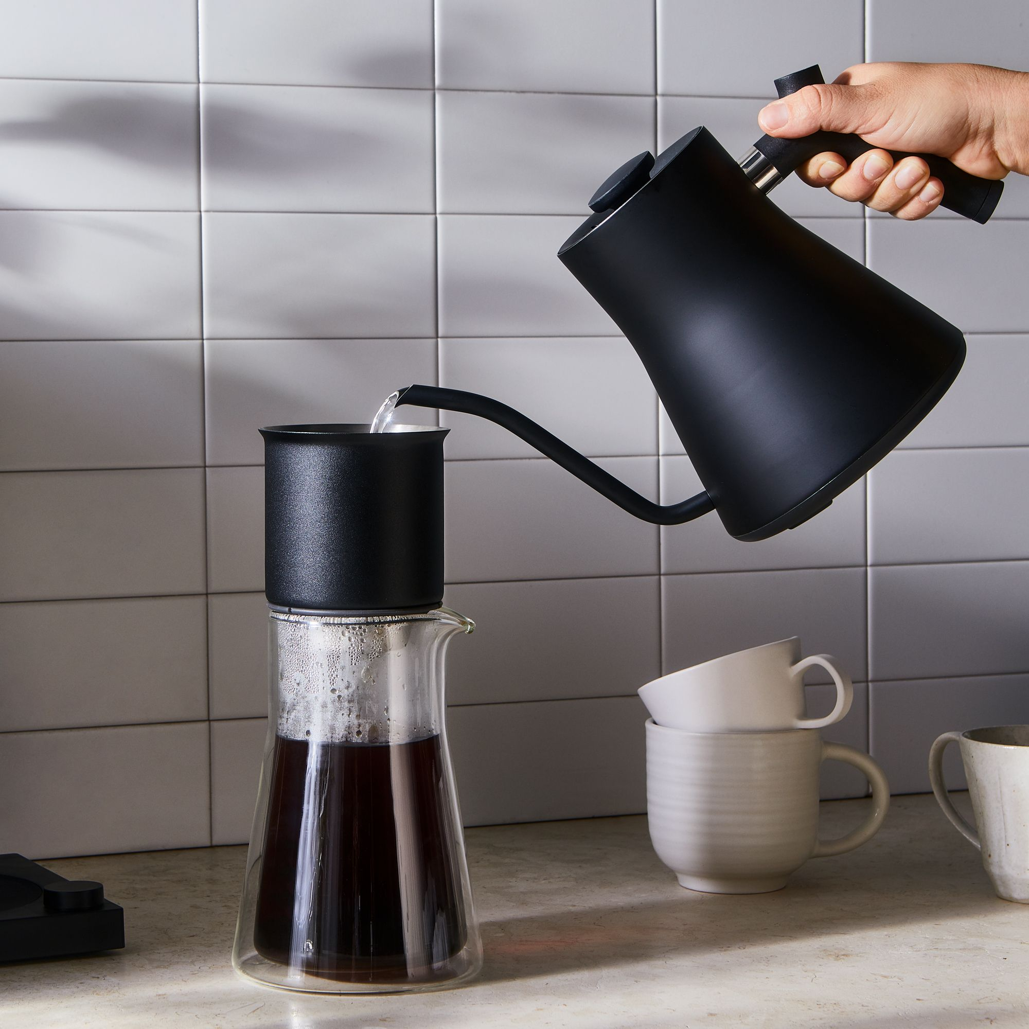 kettle pouring water into pour over coffee maker set in a glass carafe
