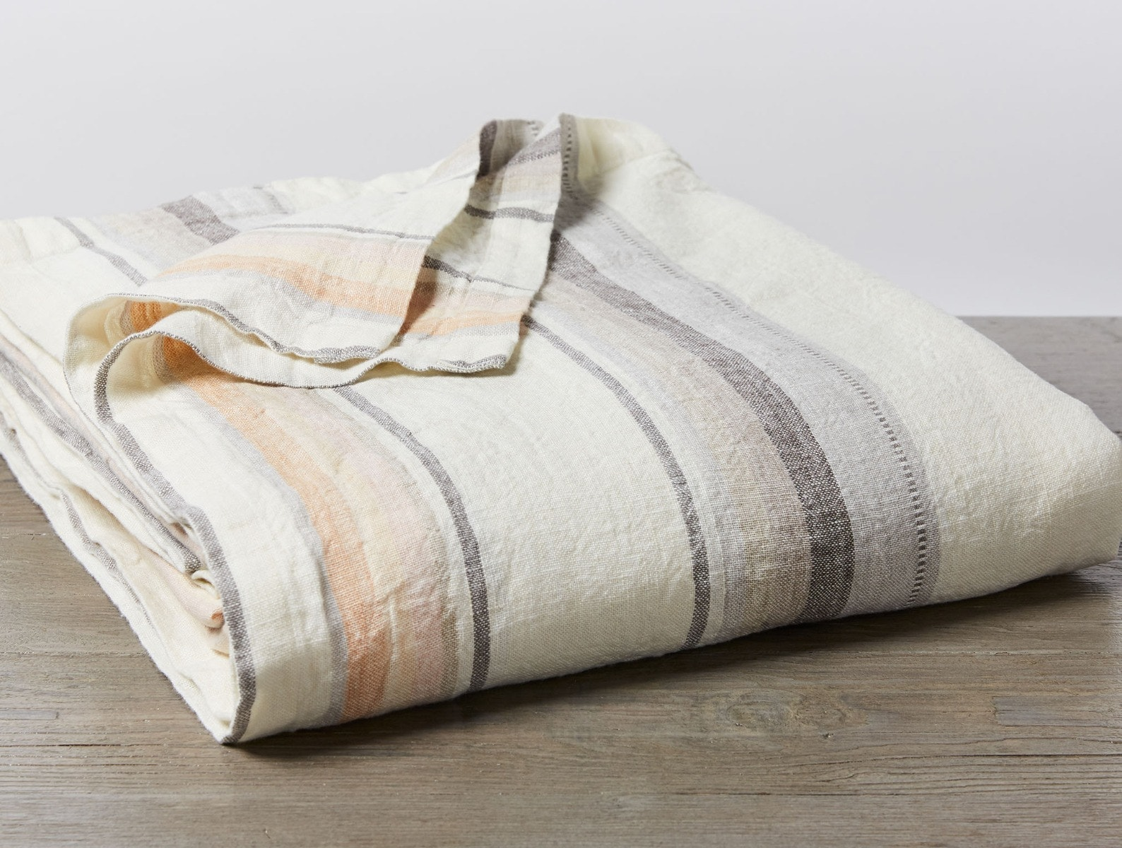 striped linen blanket on wood table
