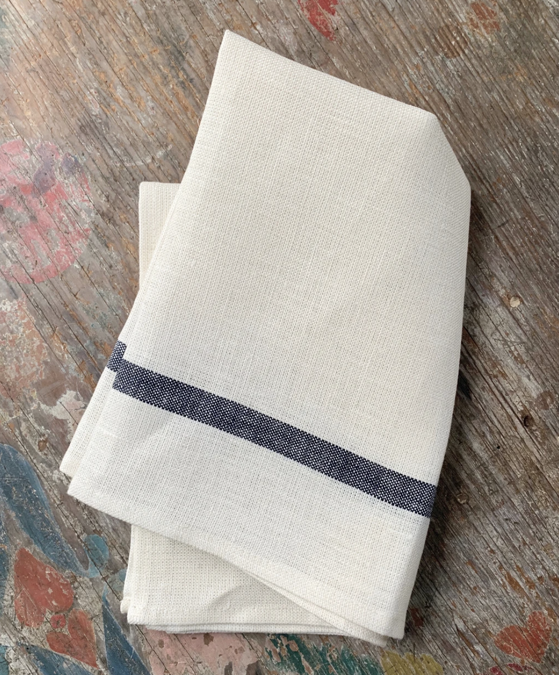 cream linen towel with navy stripe atop wood table