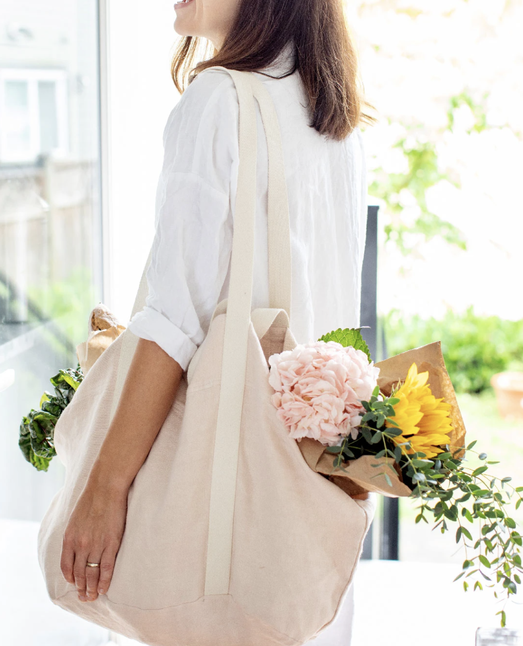 woman wearing blush linen tote with fresh flowers inside
