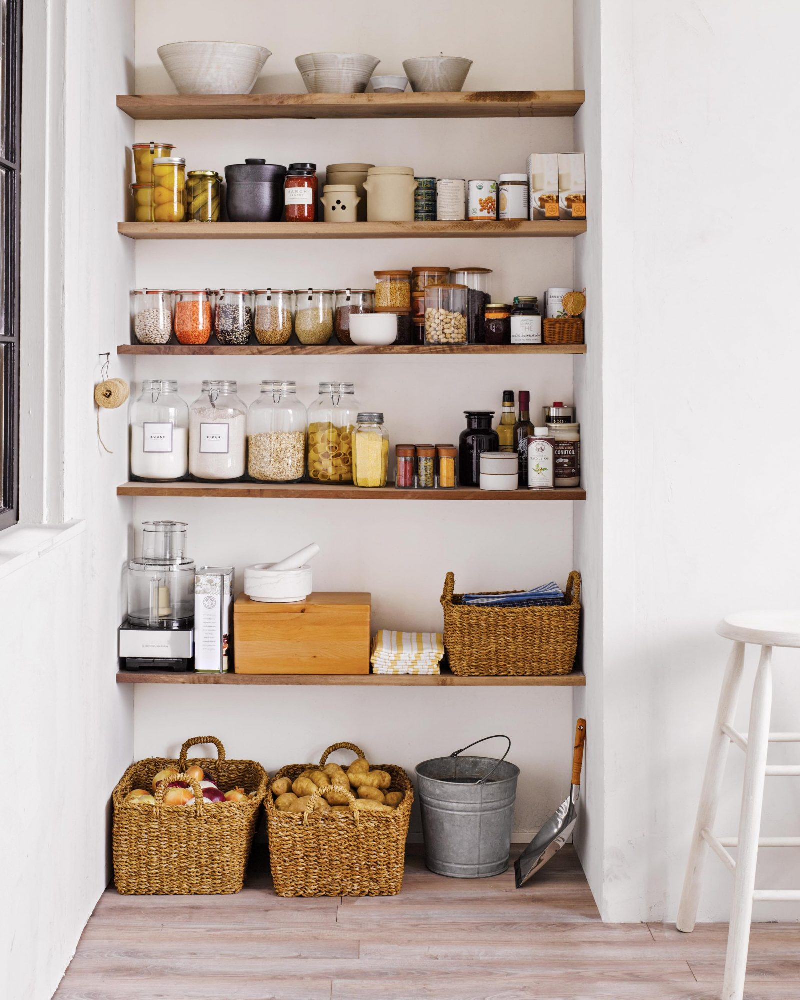 kitchen pantry with shelves stocked with jars of beans, lentils, grains, and flours