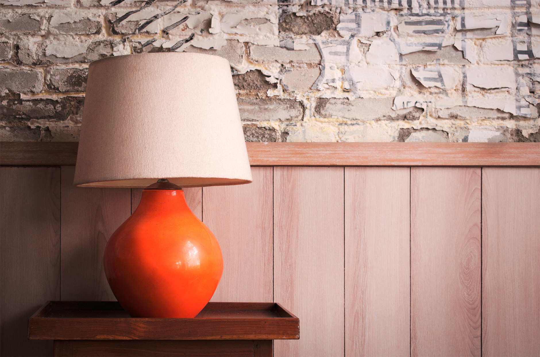 red lamp wood side table wood paneling distressed brick