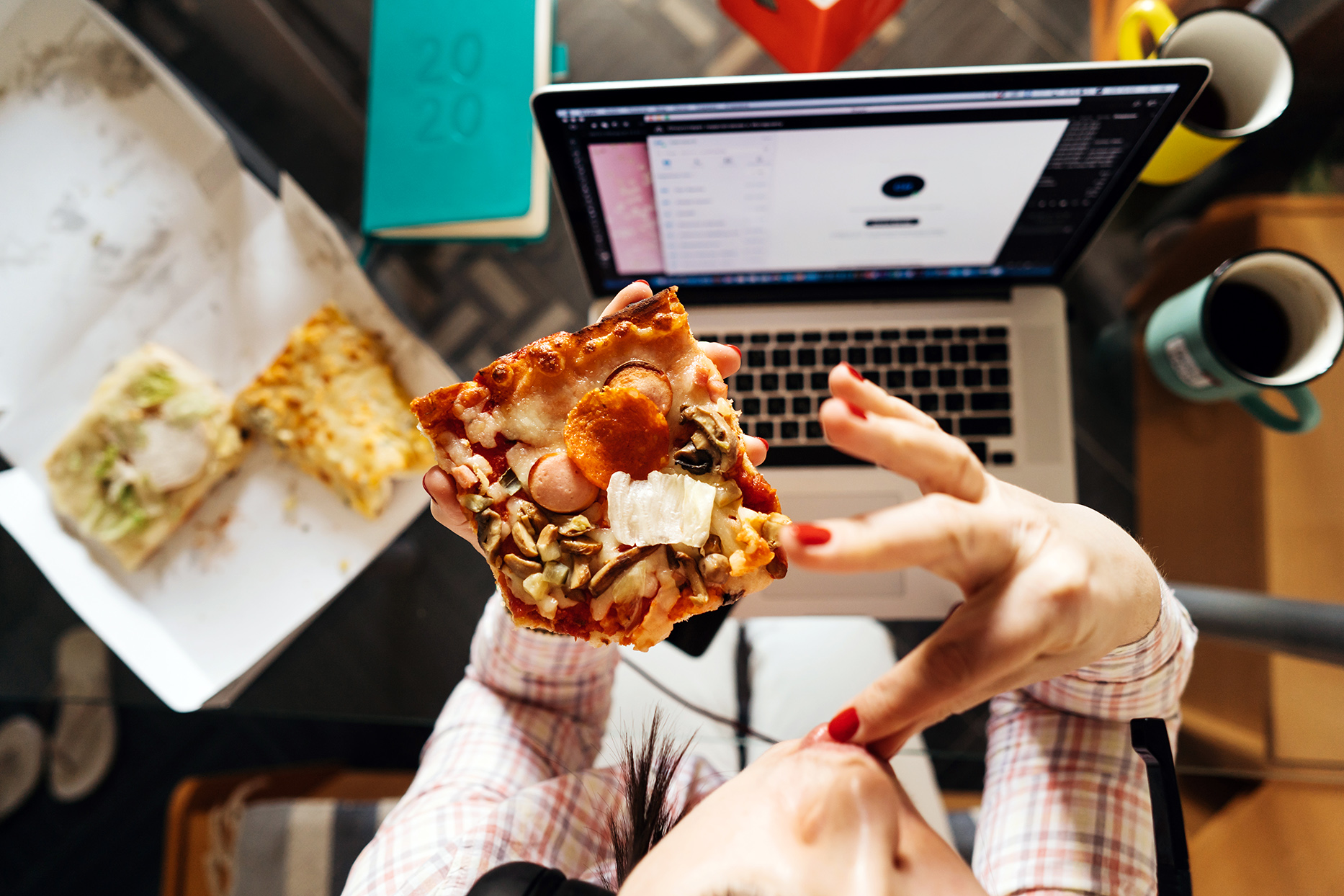 A middle-aged woman eating a slice of pizza while using laptop