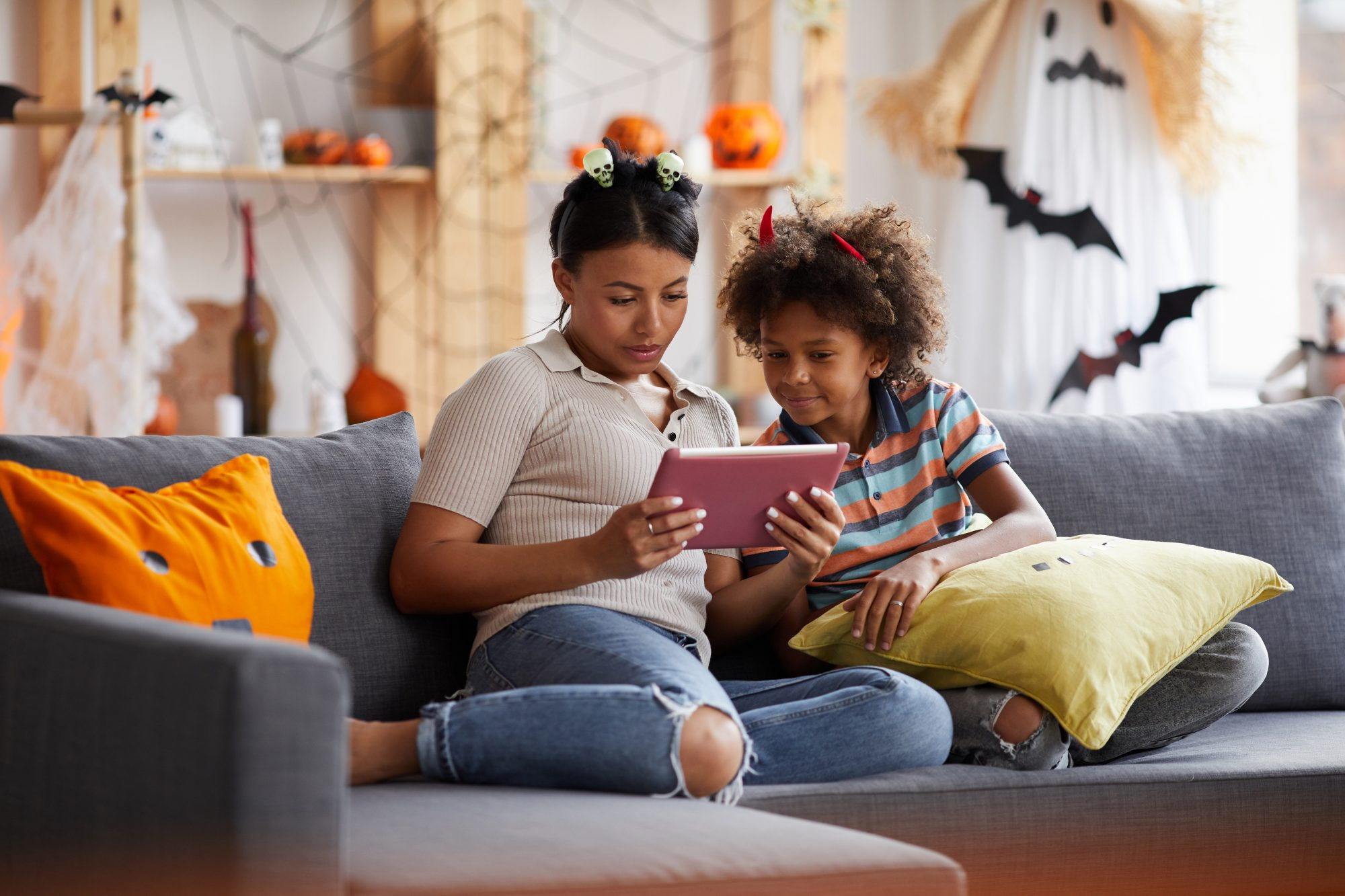 woman and child dressed for halloween holding tablet