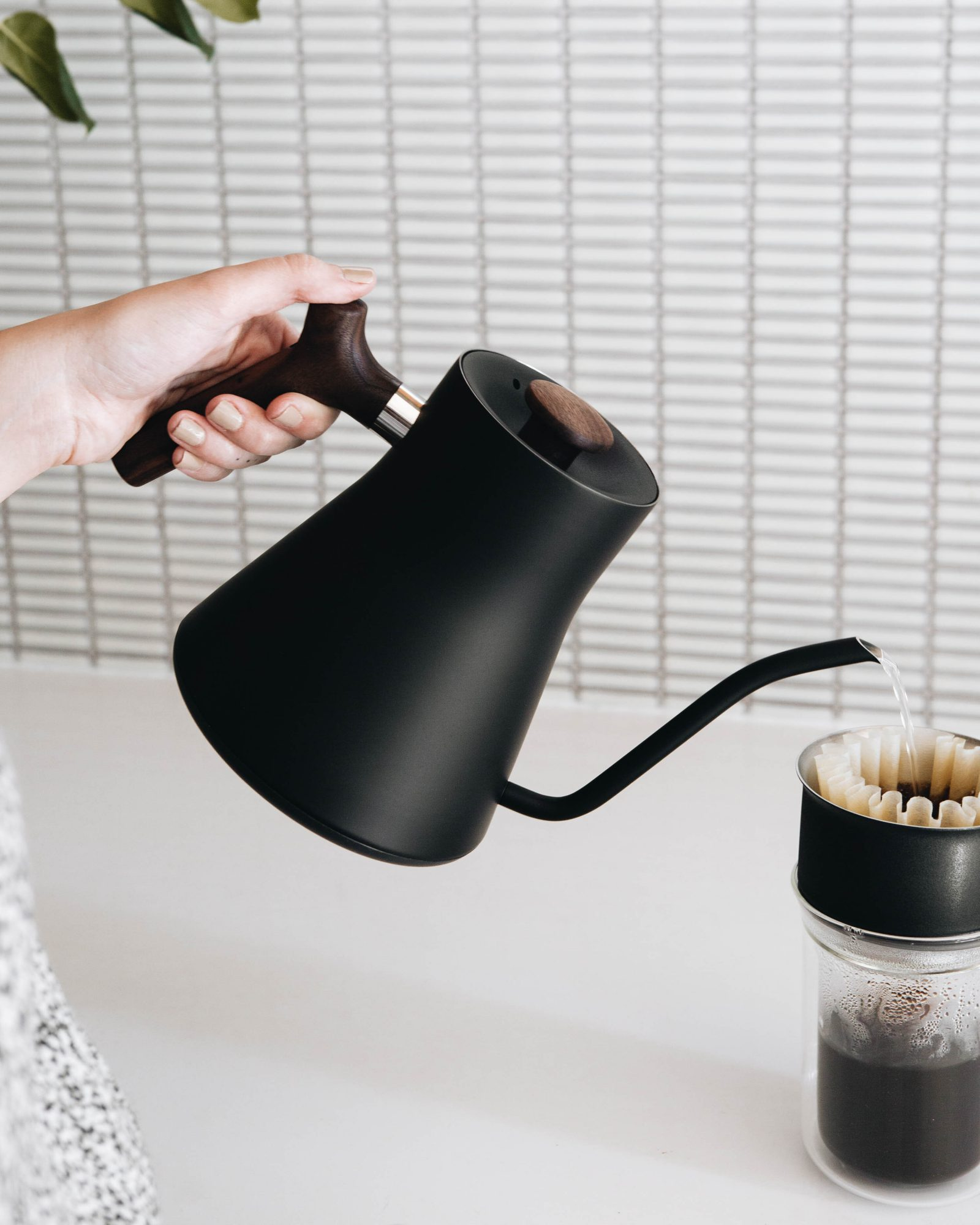 black gooseneck kettle pouring water into pourover coffee maker