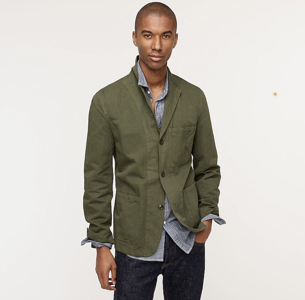 man in green linen suit jacket with blue jeans and chambray collared shirt