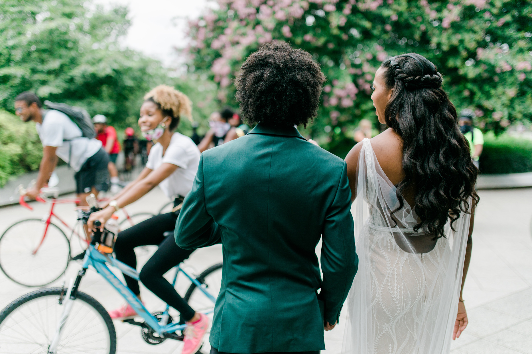bicyclists circling bride and groom