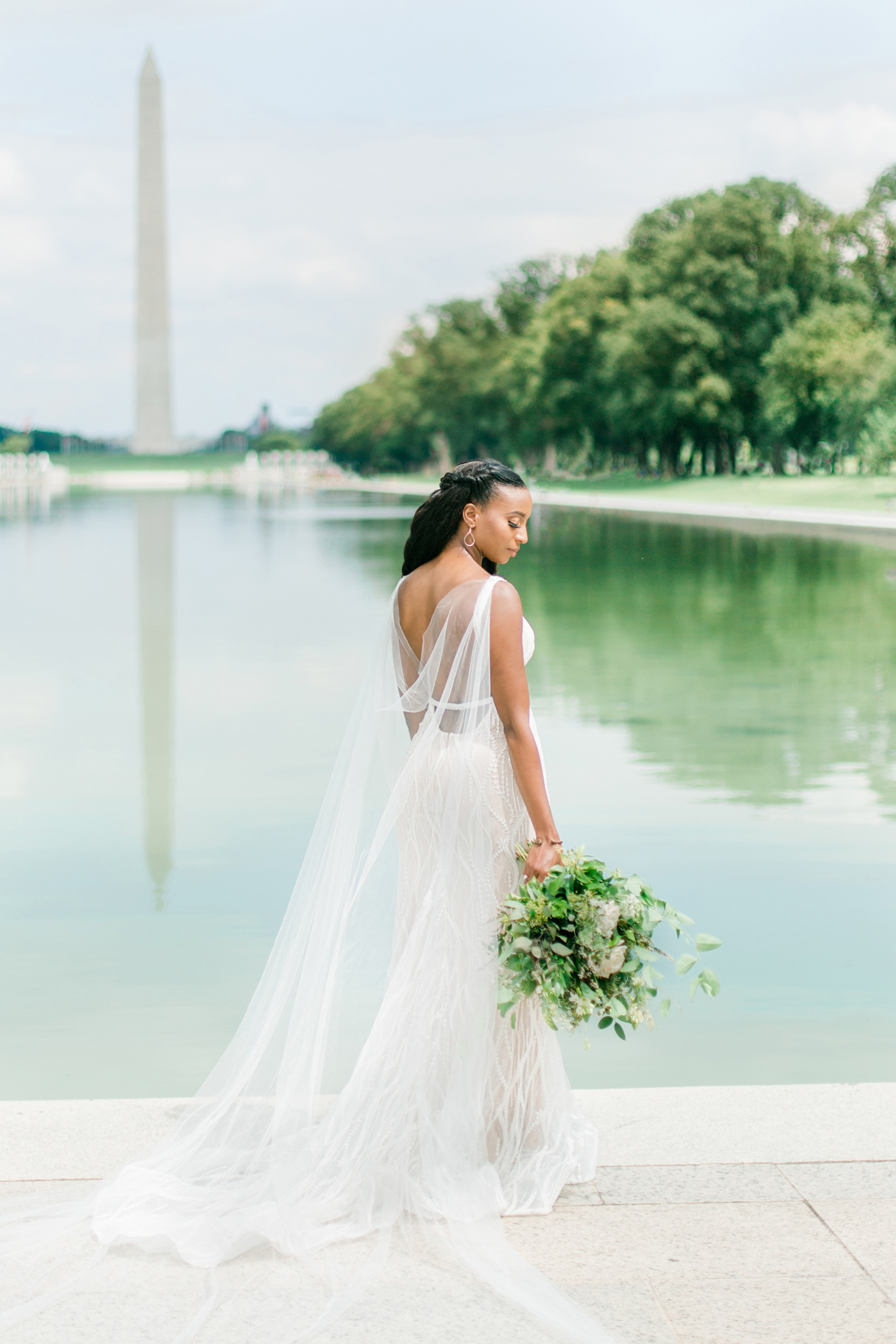 bride wearing cape posing in front of washington monument