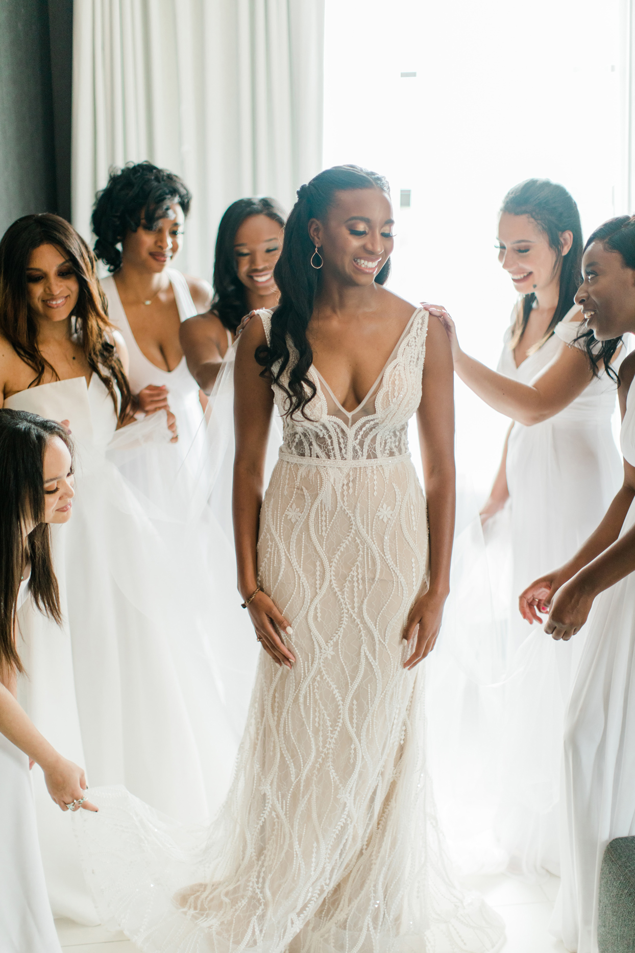 bride getting ready surrounded by bridesmaids wearing white