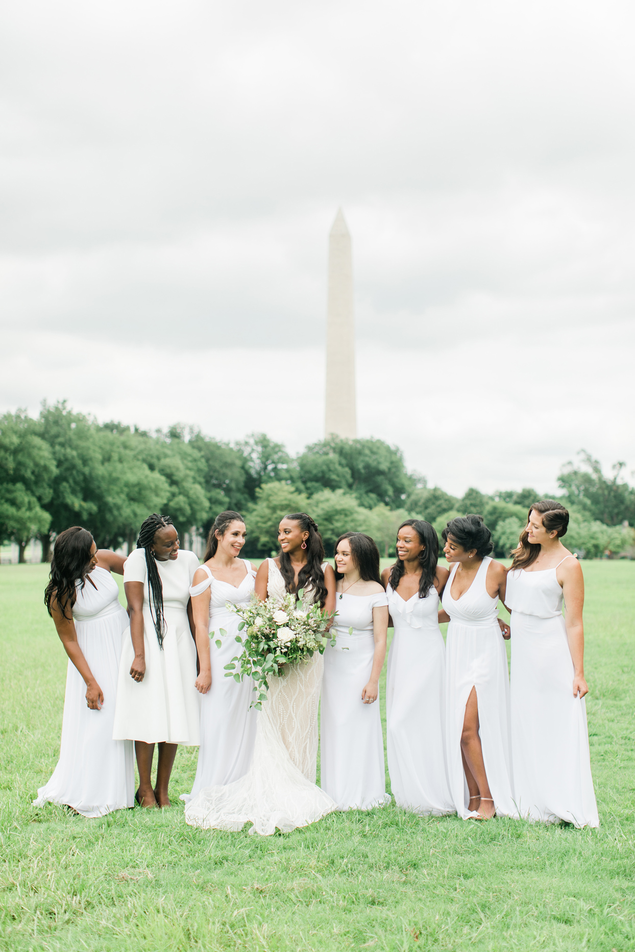 bride with bridesmaids wearing mismatched white dresses in front of washington monument