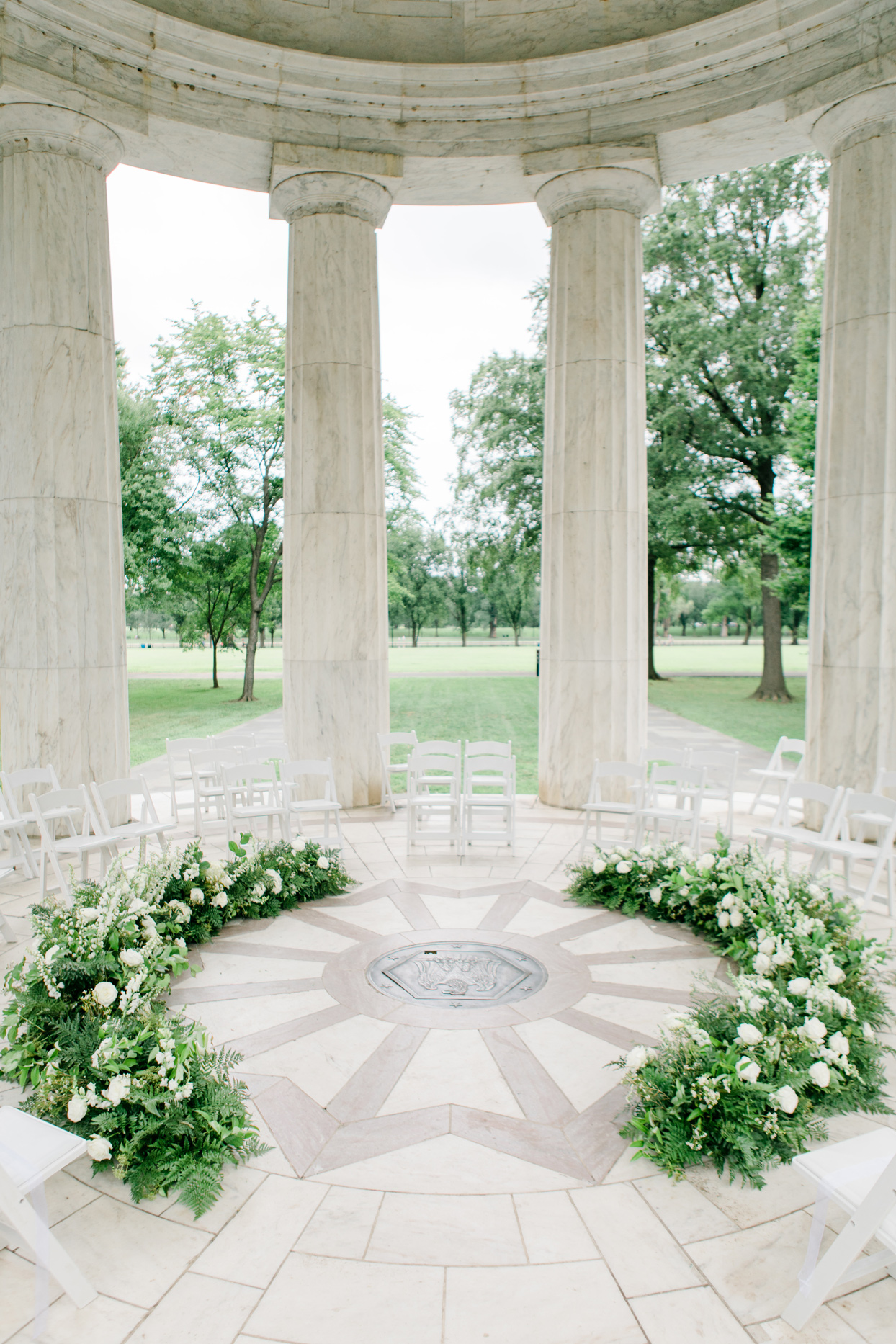 white chairs in semi-circle and greenery with white roses arranged at dc war memorial