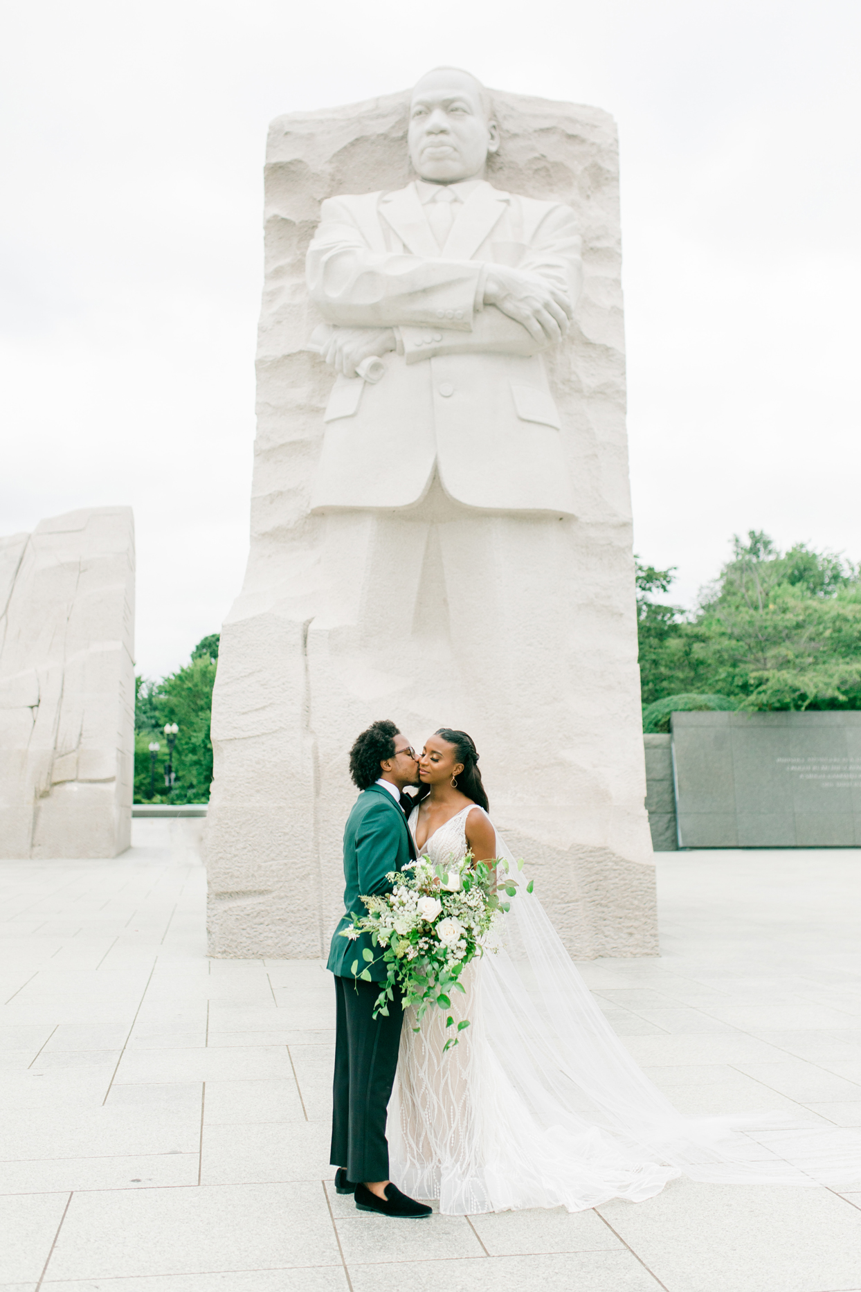 groom kissing brides cheek in front of martin luther king jr memorial