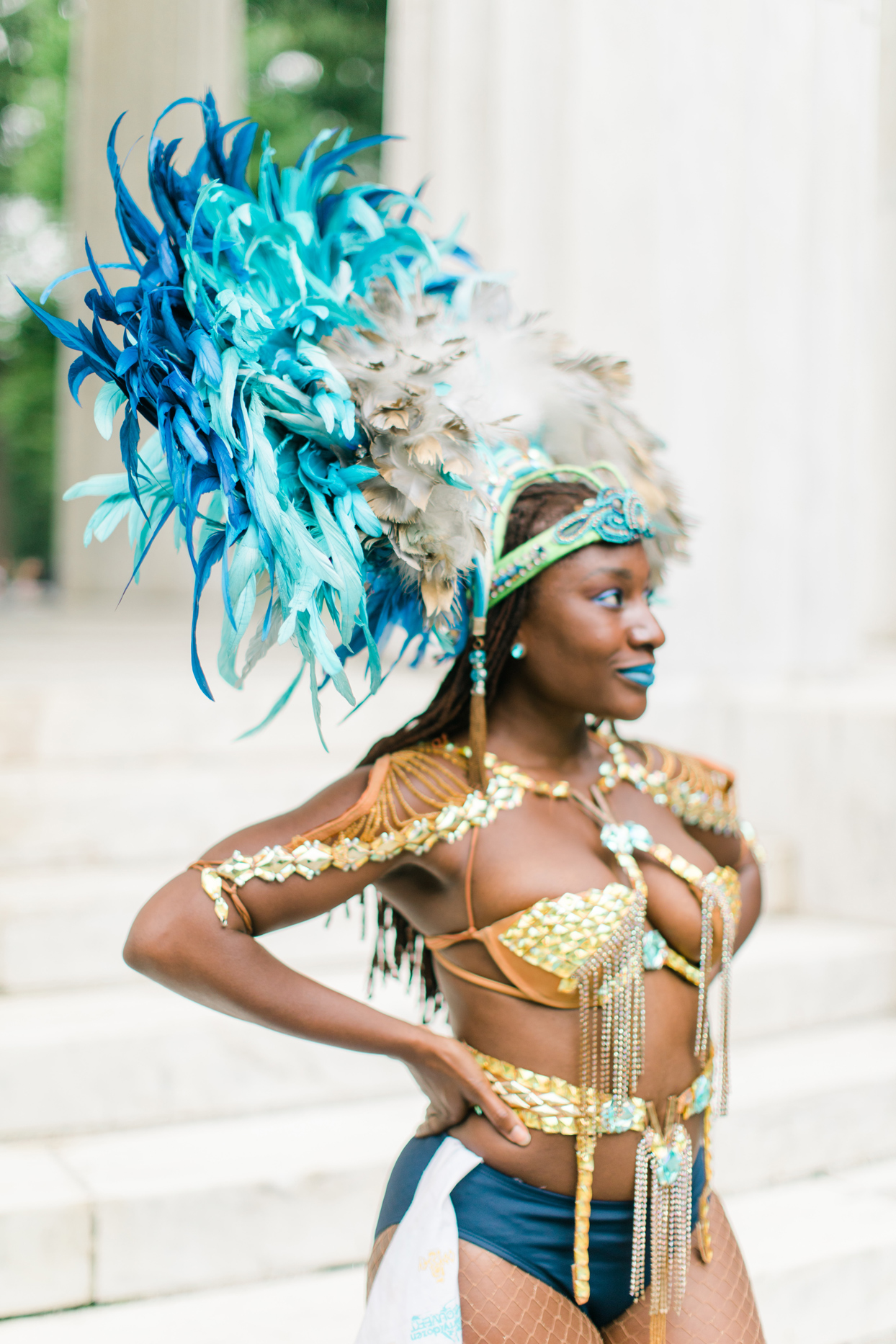 wedding soca dancer wearing blue feathers and gold jewels
