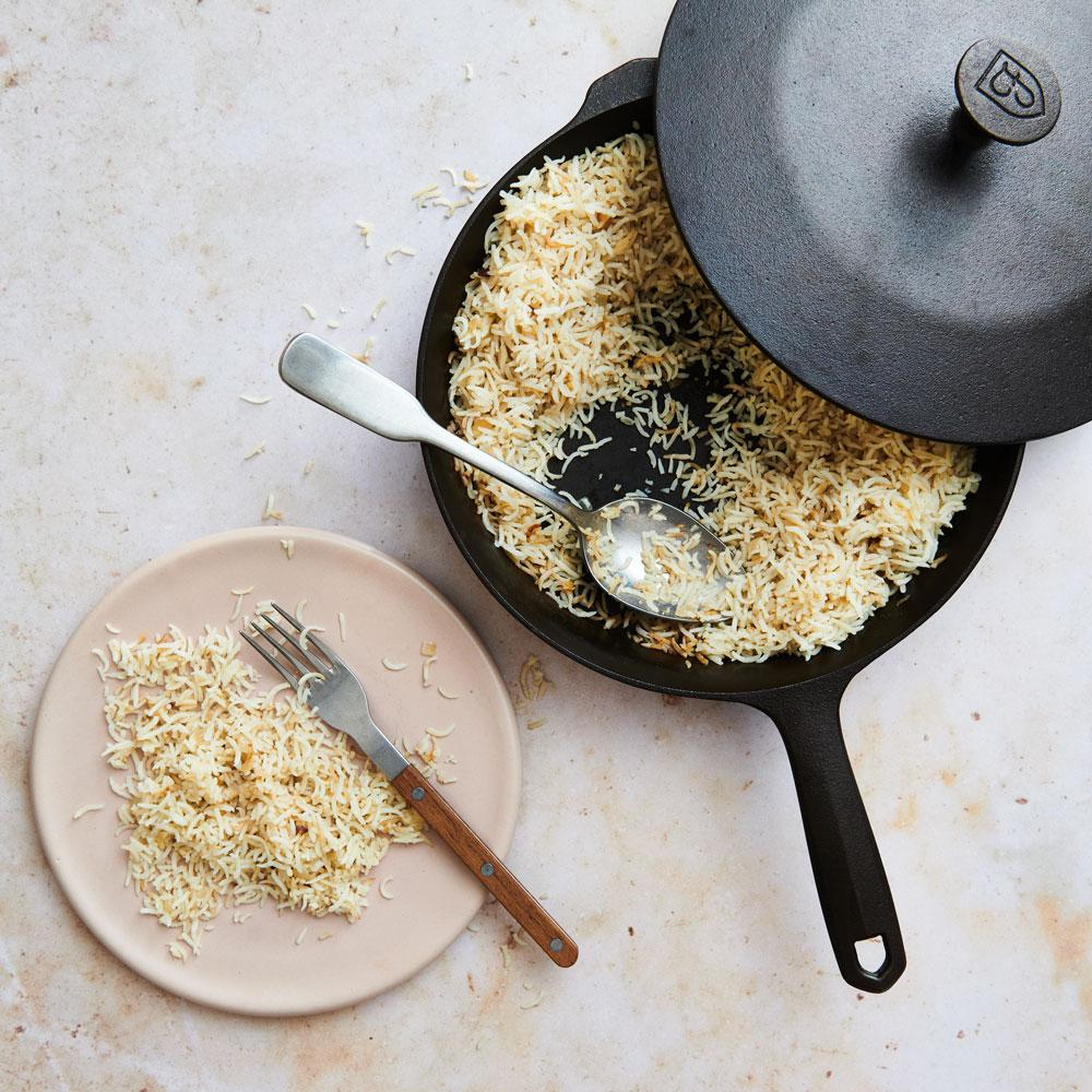large cast iron skillet and lid with rice pilaf in skillet and on a pink plate