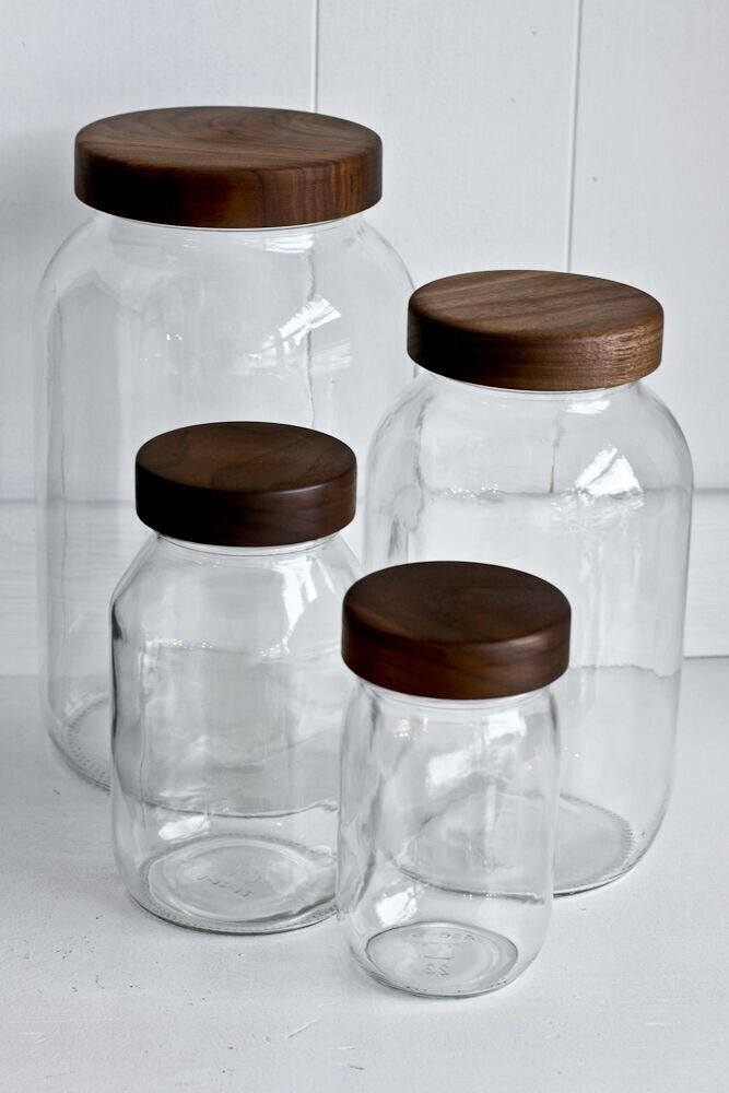 four glass jars with walnut lids on white counter