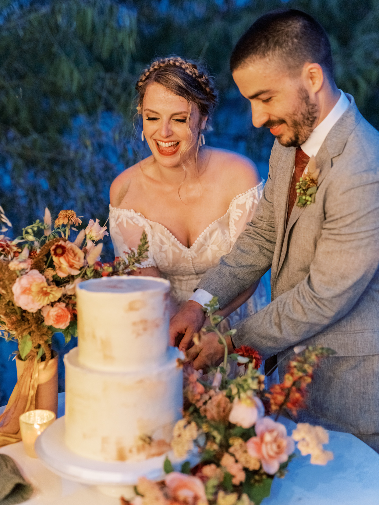 bride and groom smiling while cutting cake