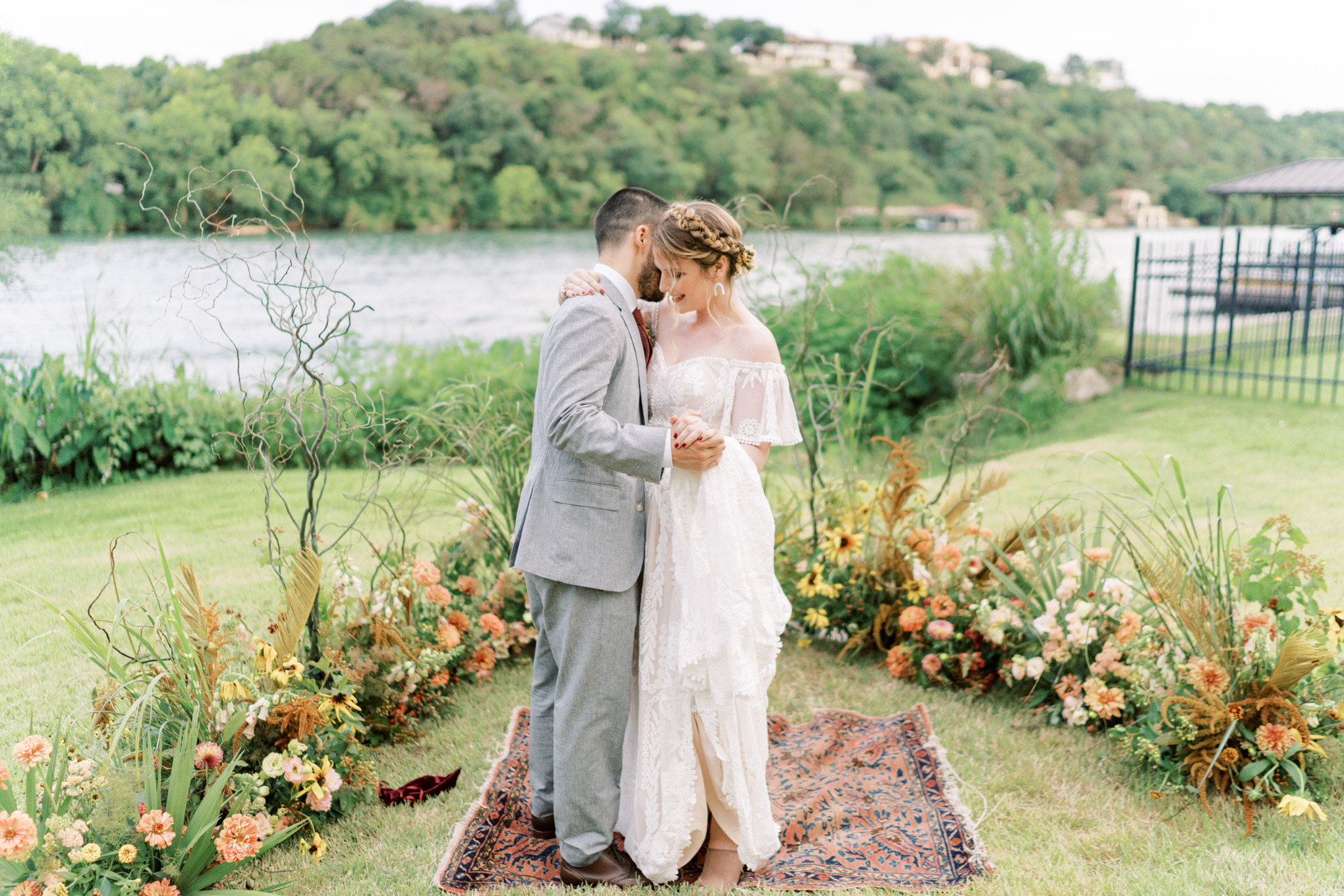 wedding couple first dance on grassy field with bohemian rug