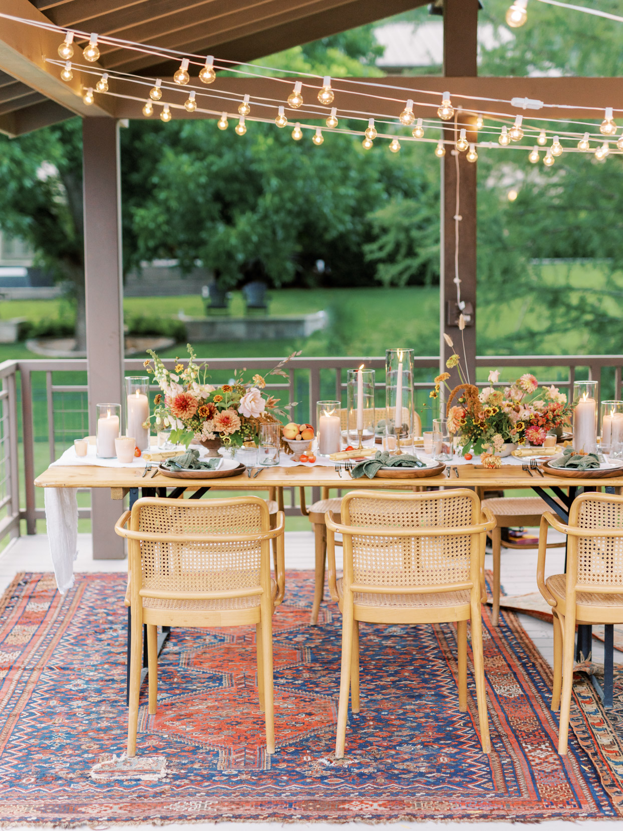 al fresco dining set up with bohemian rug and warm tones table decor