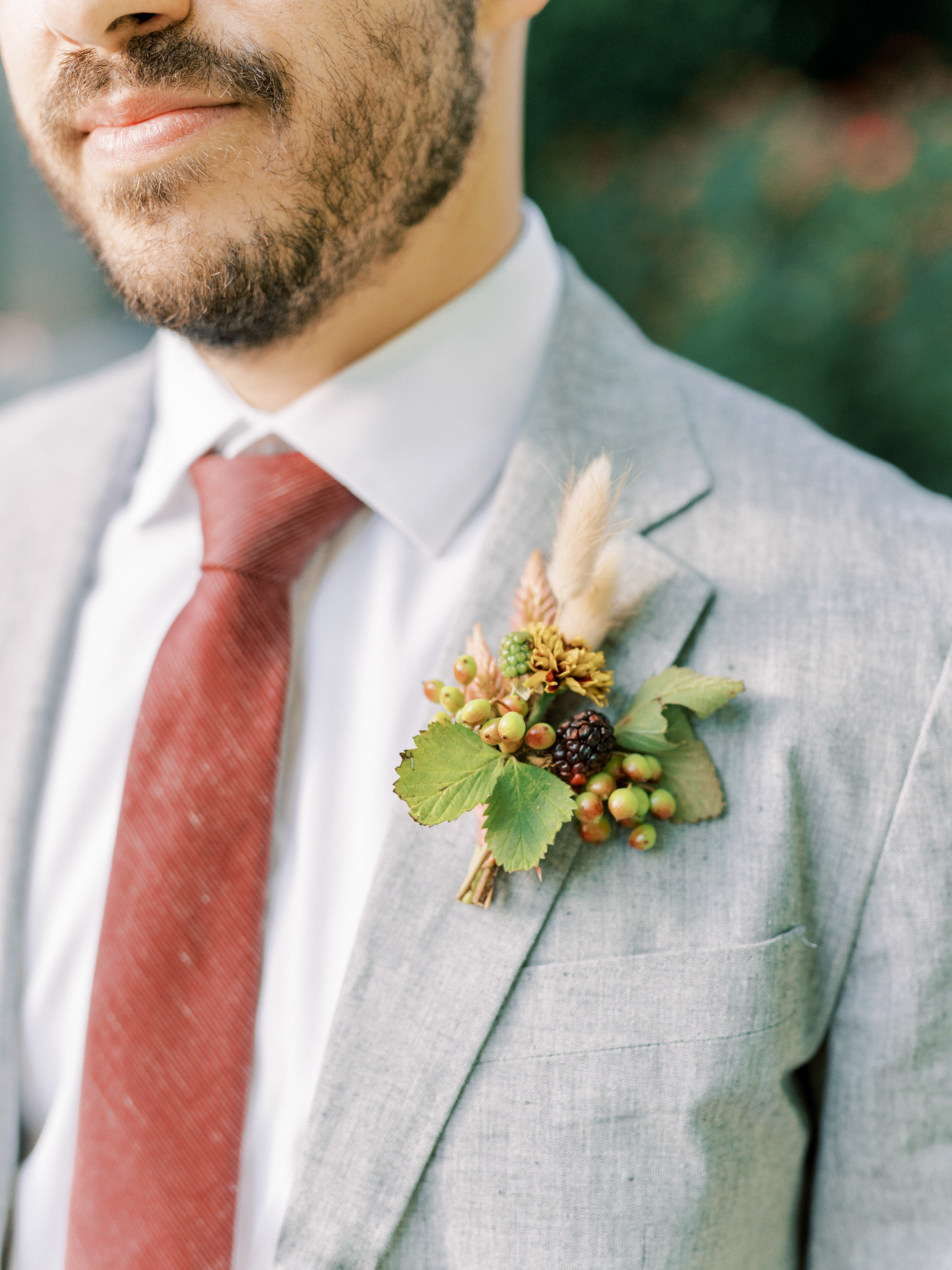 wedding groom in gray suit, red tie, with orange floral boutonniere