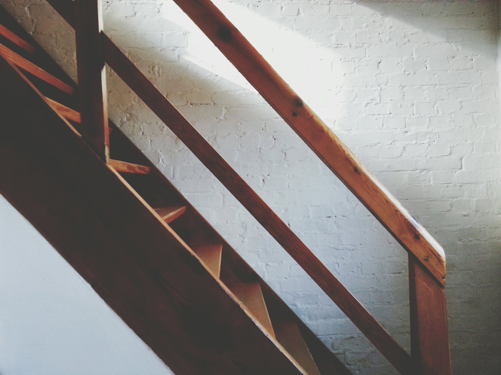 wooden staircase with railing leading to basement