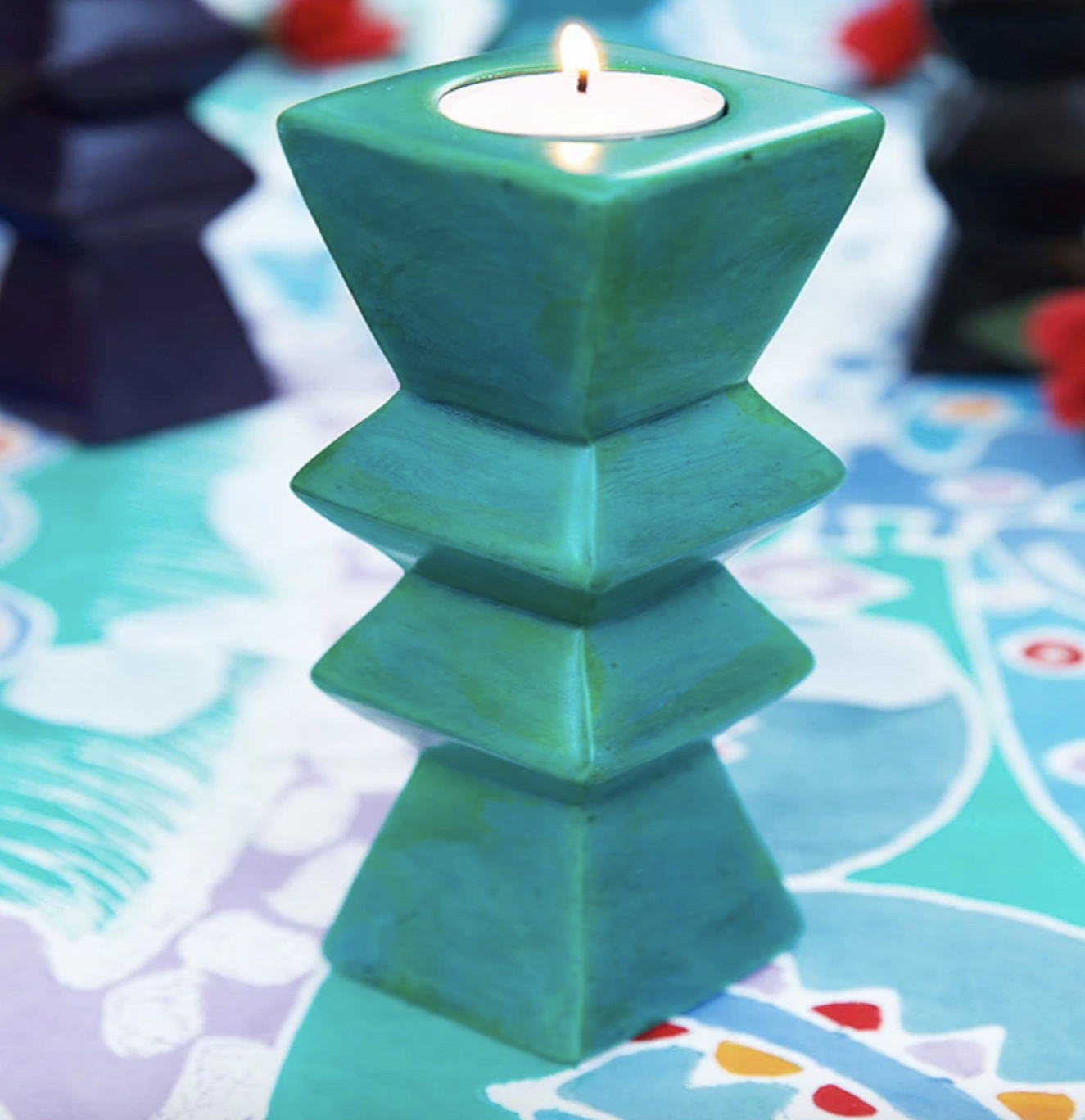green candleholder with patterned table coth