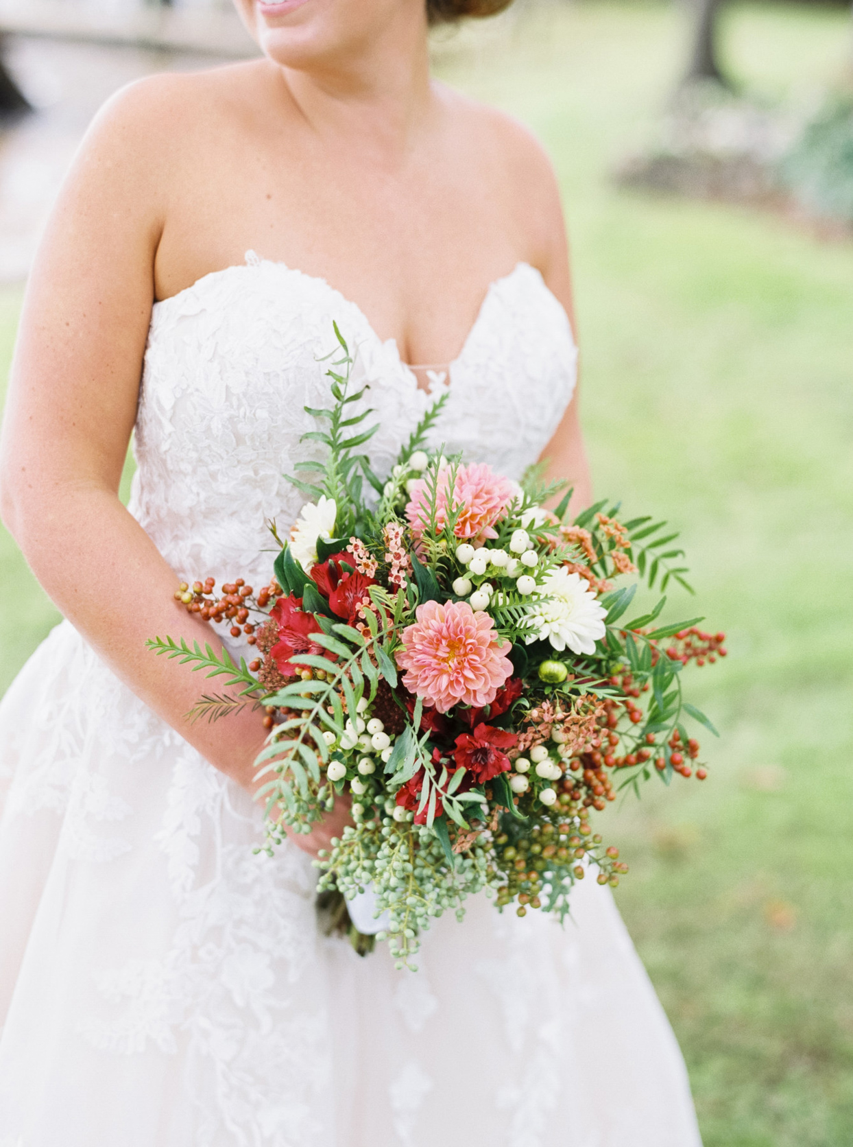 bride holding pink and red floral bouquet