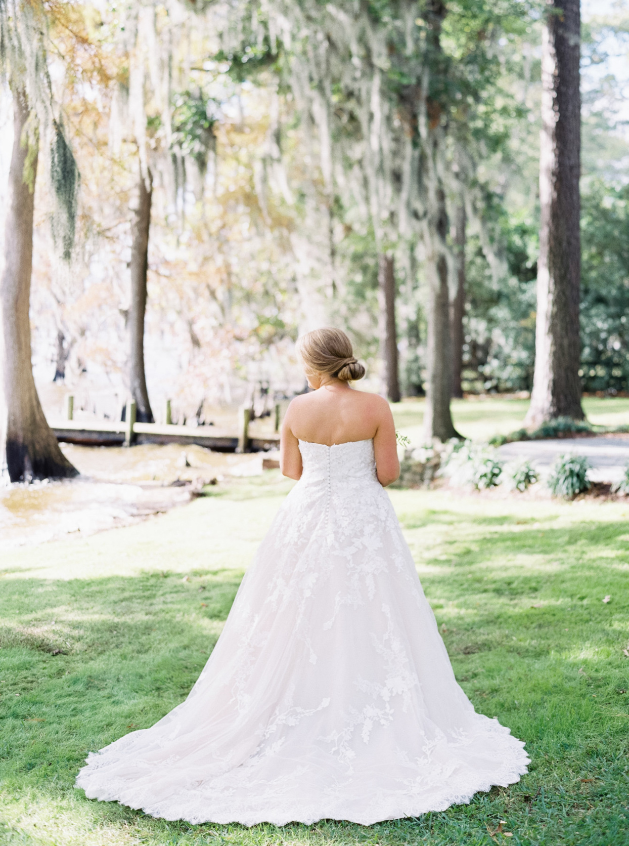 bride standing in white dress with back toward camera