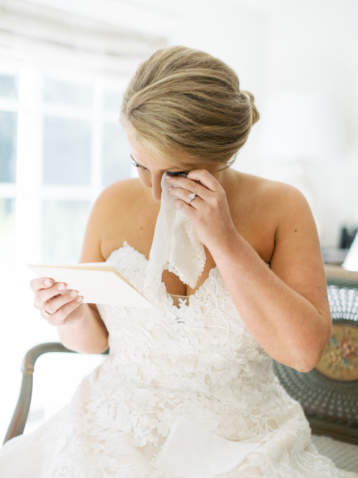 bride wiping eyes with handkerchief while reading note