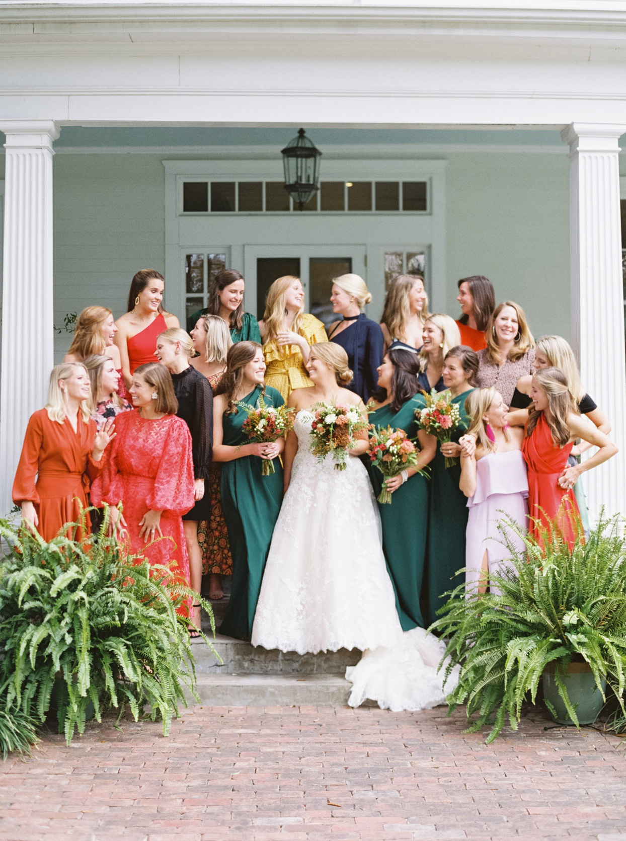 bride with bridesmaids in red and teal dresses