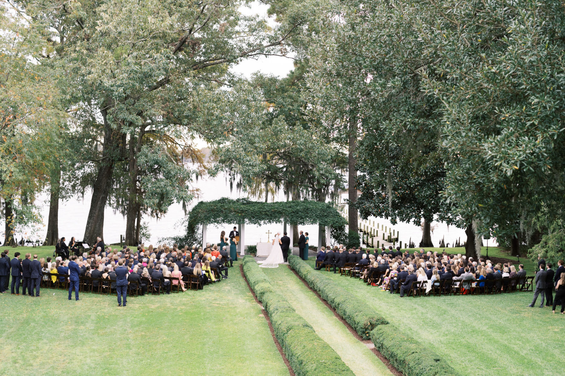 wedding ceremony by river surrounded by trees