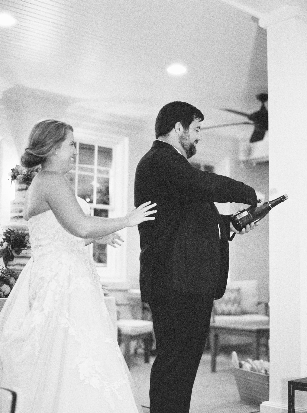 wedding couple standing on porch popping champagne