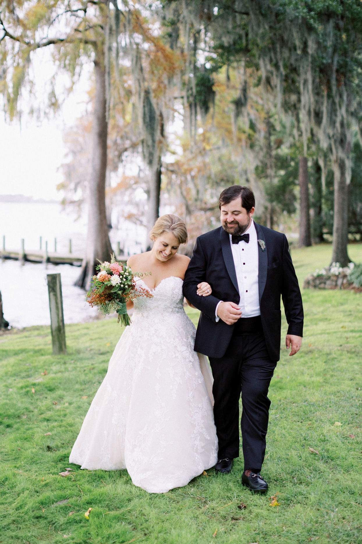 wedding couple walking arm in arm by river