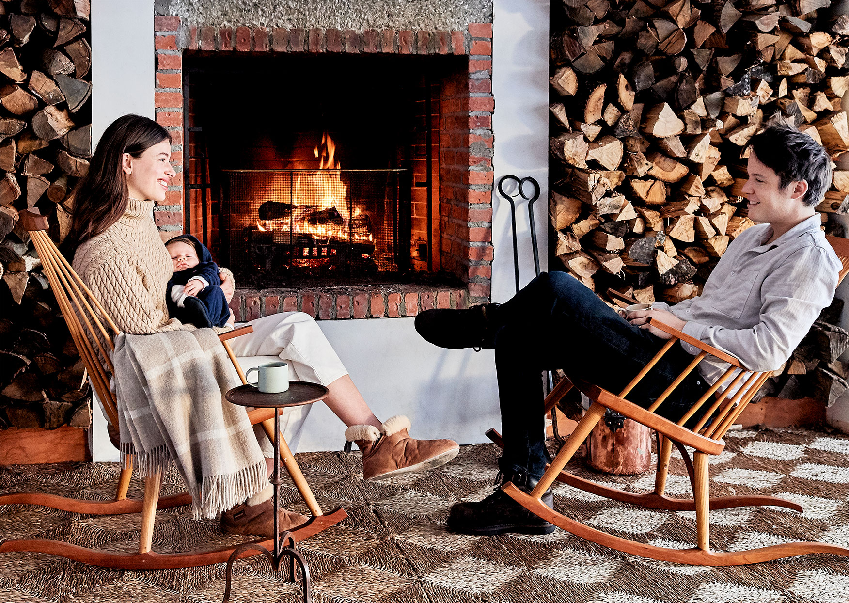 couple sitting on rocking chairs by fireplace