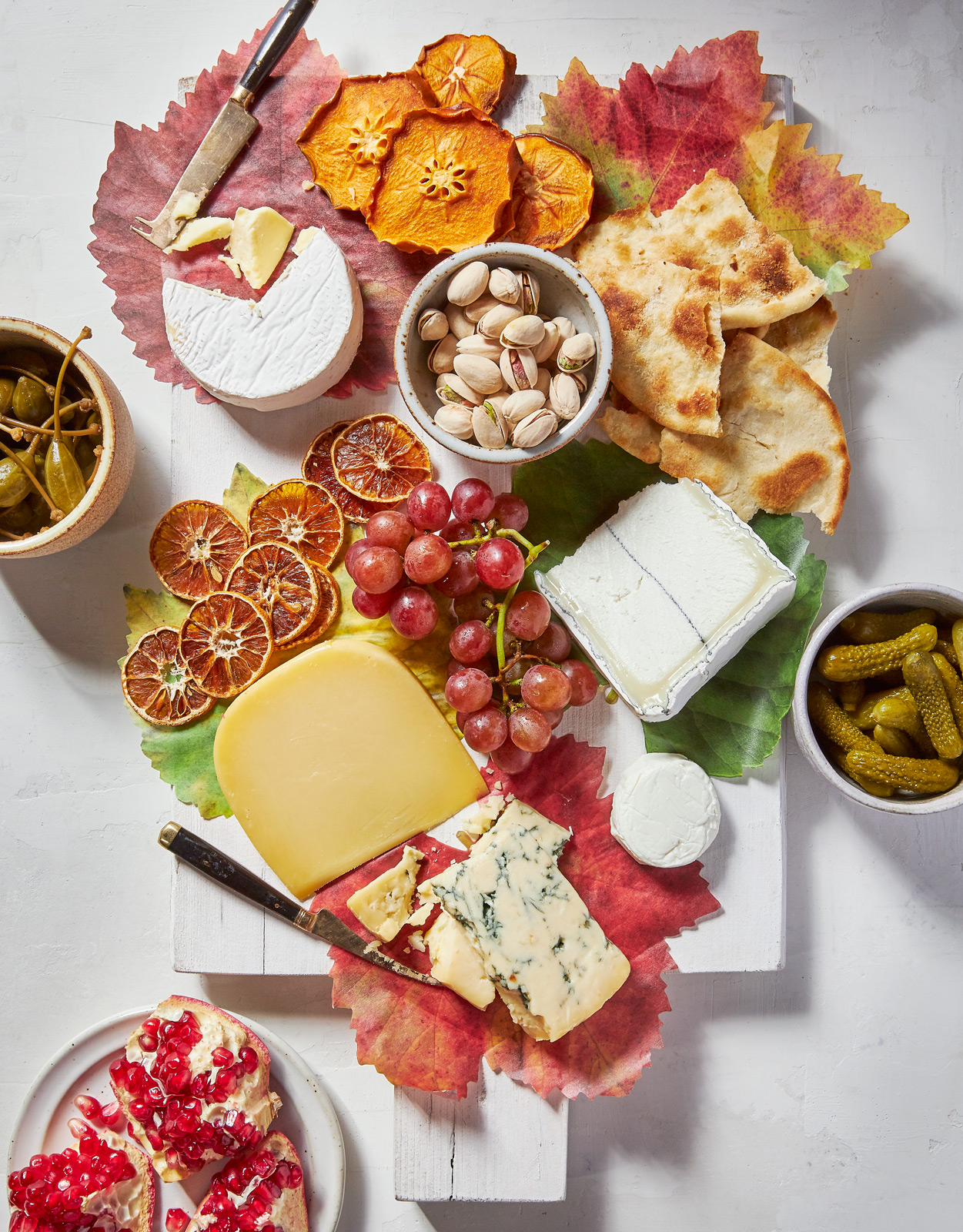 cheese board with fruit and nuts and decorated with leaves