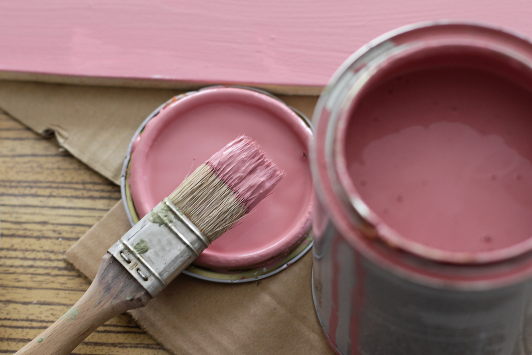 open can of pink paint with brush